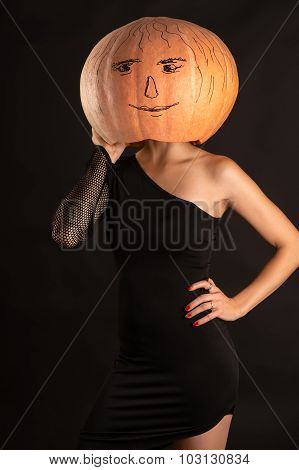 woman in a black dress with a pumpkin on head