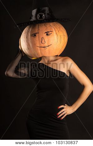 woman in a black dress with a pumpkin on head in witch hat