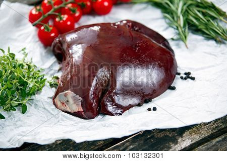Raw Liver On Crumpled Paper, Decorated With Greens And Vegetables. On Old  Wooden Table