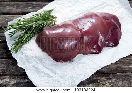 Raw Liver On Crumpled Paper, Decorated With Rosemary. On Old  Wooden Table