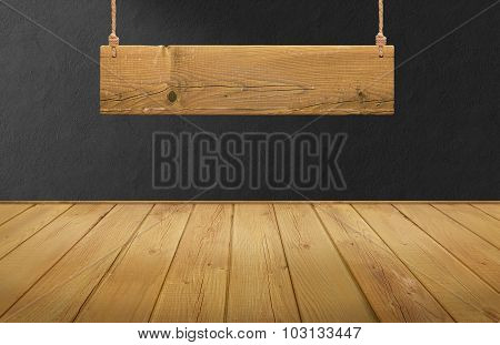 Wood table with hanging wooden sign on black concrete wall