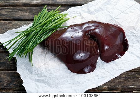 Raw Liver On Crumpled Paper, Decorated With Chives. On Old  Wooden Table