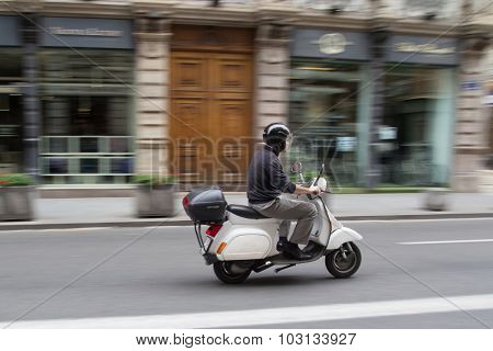 VALENCIA, SPAIN - SEPTEMBER 28, 2015: A businessman on a scooter in the city center of Valencia. Due to the economic crisis, scooter sales in Europe have declined 20 percent in the year 2014.