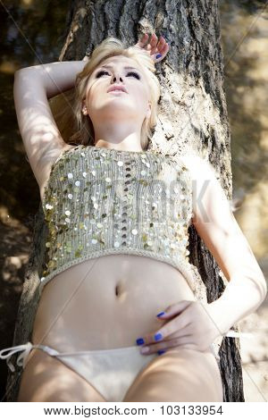 Portrait of a beautiful young adult attractive sexy and sensuality pretty blonde woman in gold blouse dress and panties in sunny summertime green garden