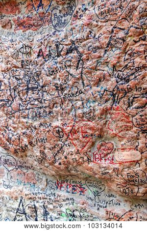 VERONA, ITALY - SEPTEMBER 2014 : Shallow DOF of a stone wall full of names and love declaration near Juliet's house in Verona, Italy on September 13, 2014. Photo focus on the upper part