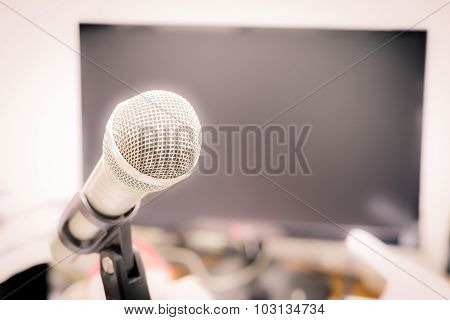 Microphone On The Background Of Blurred Computer Screen In Office. Soft Focus .shallow Depth Of Fiel