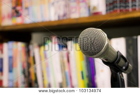 Microphone On The Background Of Blurred Bookshelf  In Library. Soft Focus .shallow Depth Of Field. V