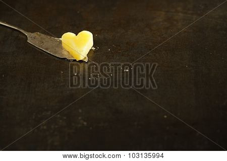 ghee or melted butter in heart shape on knife and dark metal backdrop