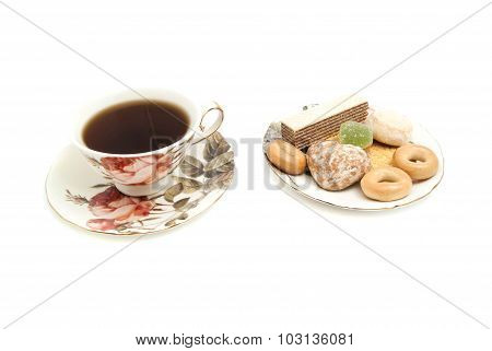 Mug Of Tea And Tasty Sweets On White