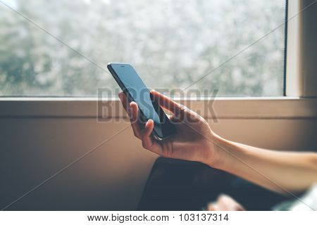 Man using his smartphone close the window