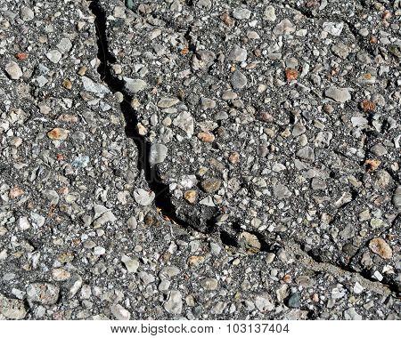 Paved asphalt surface with a large crack