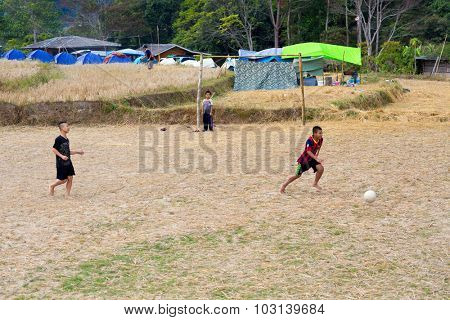 MAE KLANG LUANG, THAILAND, DECEMBER 31, 2014 : Some kids are playing soccer football in a dry harvested rice field in the village of Mae Klang Luang,  Doi Inthanon national park, Thailand