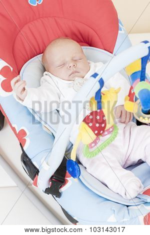 one month old baby girl sleeping in baby''s chair