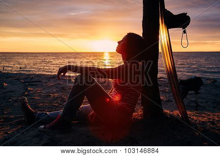Yong woman sitting on the shore with wakeboard