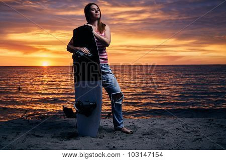 Yong woman standing on the shore with wakeboard
