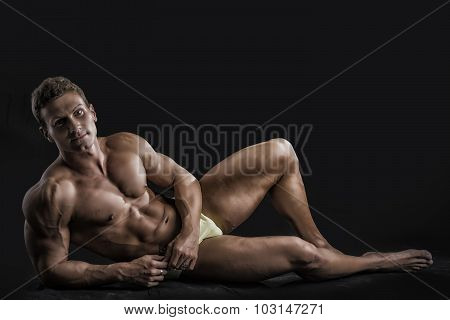 Muscular young bodybuilder laying down in relaxed pose, smiling
