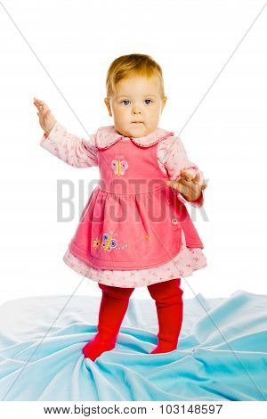 Baby Girl Standing On A Blue Blanket. Studio Photo