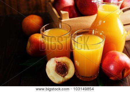 Peach juice and ripe peaches on wooden background