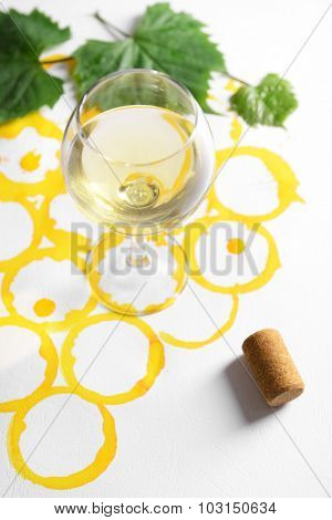 Wine goblet and corks on picture painted with wine