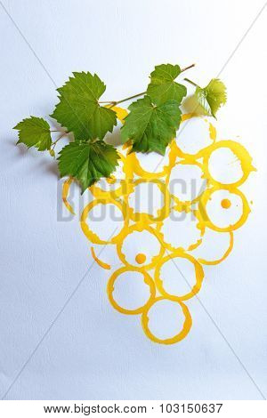 Branch of grapes painted with stains of wineglass on white paper background
