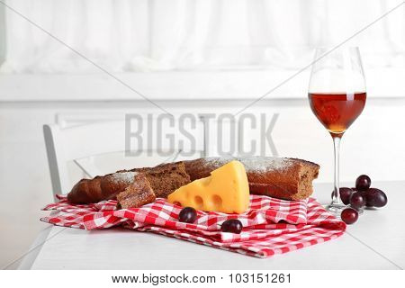 Glass of wine with bread and grapes on table in kitchen