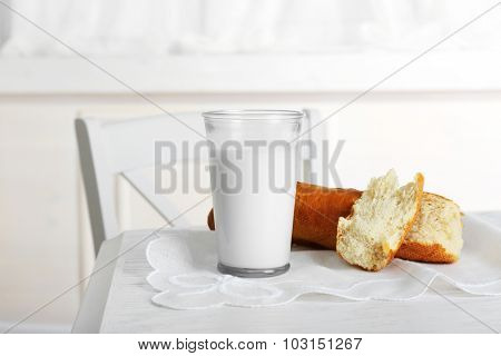 Milk with bread on table in kitchen