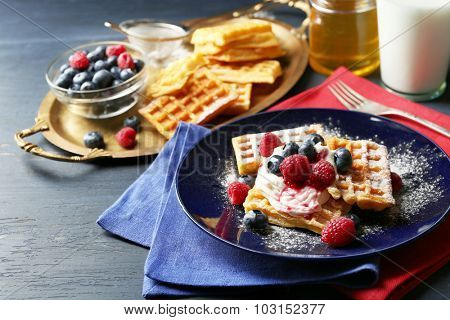 Sweet homemade waffles with forest berries and cream on plate, on dark wooden background