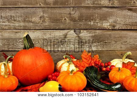 Autumn leaves, pumpkins and vegetables against an old wood background