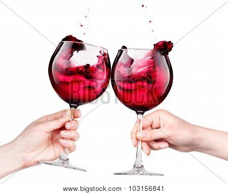 Glasses of red wine with splashes in hand isolated