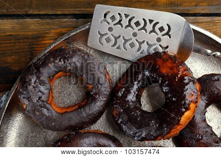 Delicious doughnuts with chocolate icing on metal tray close up