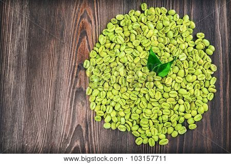 Green coffee beans with leaves on wooden table close up