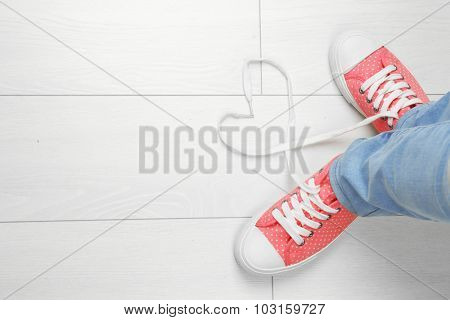 Female feet in gum shoes on wooden floor background