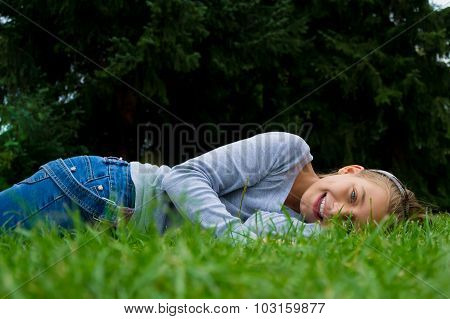 Young Cute Child Girl Lays On Stomach In Summer Grass Smiling