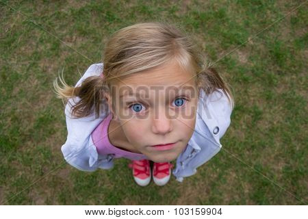 Child Girl Face From Above Perspective Shot Outside On Grass