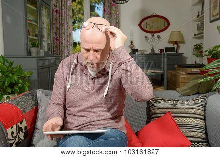 A Senior Man With A Digital Tablet On The Sofa
