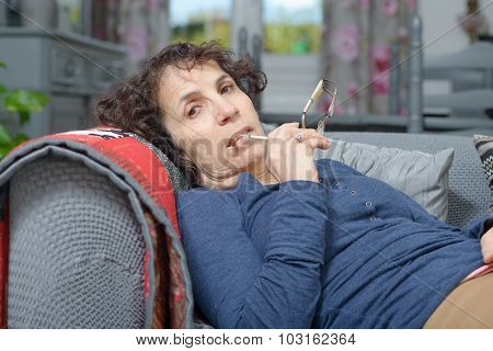 A Sick Woman Sleeping On A Sofa In Her House