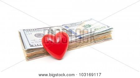 Red heart next to pile of dollar notes