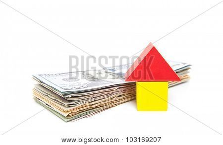 Stylized home next to pile of dollar notes