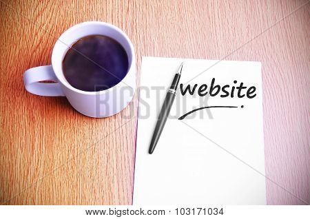 Business Concept - Steamy Coffee And Black Pen With White Paper Written Website
