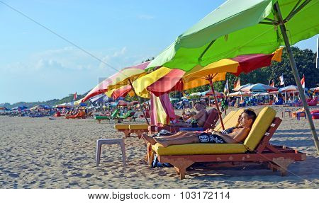 Tourists Snooze On Recliner Chairs At Legian Beach, Bali
