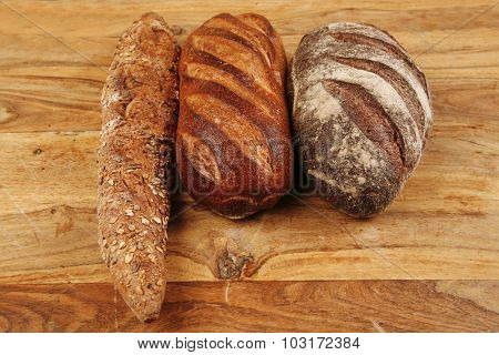 different rye and white flour bread loaf with french fresh baguette on light wooden table background