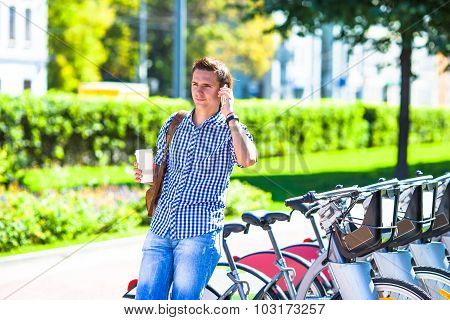 Young man with glass of coffee on bike outdoor