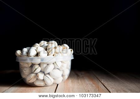 Pistachio put in bowl on the wood floor
