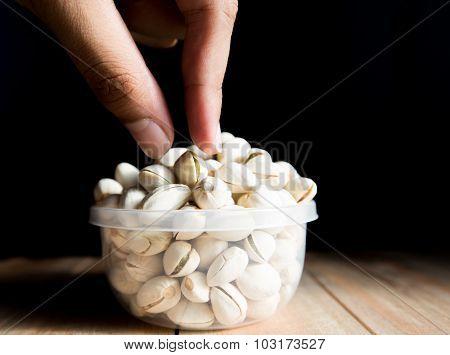 Human's hand pick up pistachio