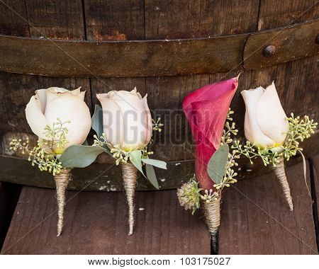 white roses groomsmen boutonniere and pink grooms lily wooden background