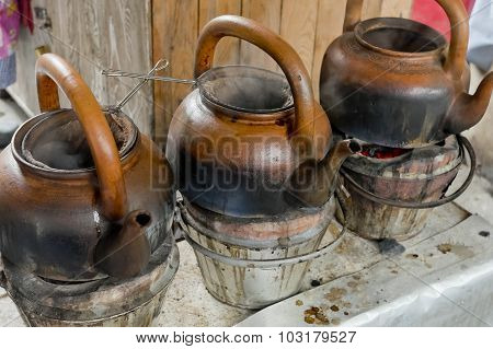 Baked Clay Kettle With Hot Water On Stove.