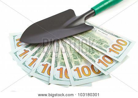 Hundred-dollar bills and garden shovel