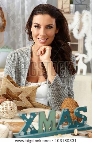 Young woman sitting at table, sorting christmas decoration, smiling happy, looking at camera.