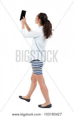 a side view of a woman walking with a tablet PC is in the hands of beautiful curly girl in motion.  backside view of person.  Rear view people collection. Isolated over white background.