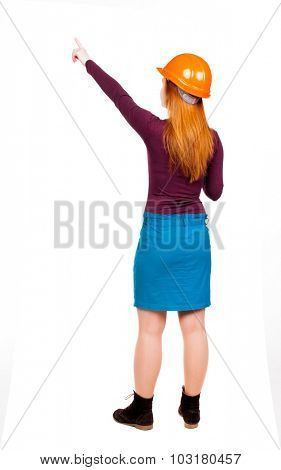 Back view of  pointing young women in helmet. Young girl gesture. Rear view people collection.  backside view of person.  Isolated over white background. The woman builder gives teams.
